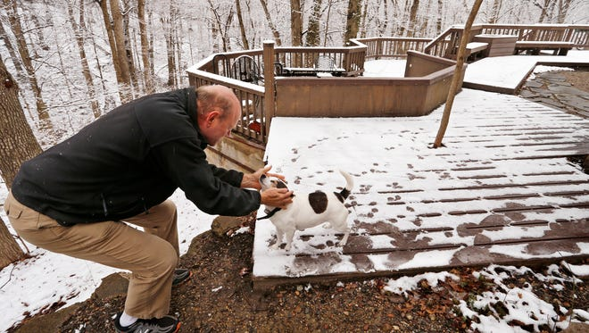 """Kevin Kaufman gives his dog Jackie a scratch behind the ears as he enjoys the view of the snow covered trees from the back deck of his home on Hollowood Drive in Happy Hollow Heights Monday, April 9, 2018, in West Lafayette. """"This is one of my favorite parts about living here, because of the snow,"""" said Kaufman."""