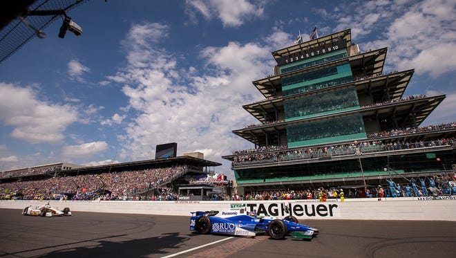 IndyCar driver Takuma Sato crosses the finish line two-tenths of a second before driver Helio Castroneves, winning the 101st running of the Indianapolis 500 at Indianapolis Motor Speedway, Sunday, May 28, 2017.