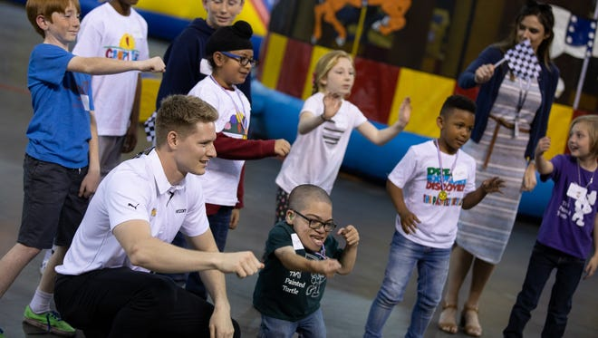 Team Penske driver Josef Newgarden plays with campers from the Camp SeriousFun program earlier this year in California. Newgarden is IndyCar's ambassador to SeriousFun, its new charitable partner.