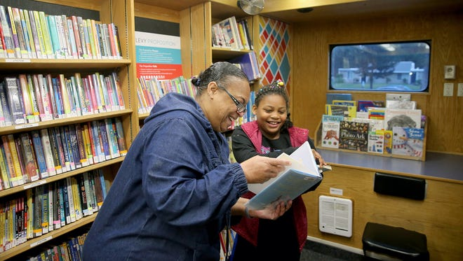Renee and Da-Mira Thomas look at library books from the bookmobile outside their Central Kitsap apartment in November 2017. The library is discontinuing its bookmobile.