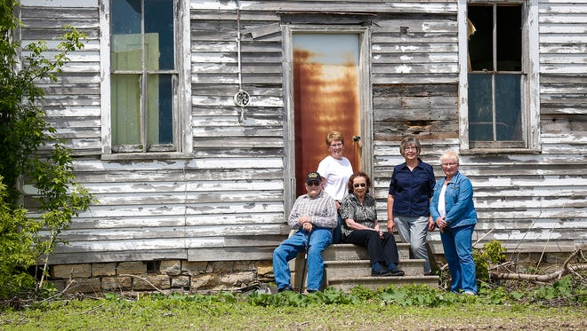 Former Round Prairie School students Lyle Lindeman, Sharon Tavs-Krohn (left) Wanda Tavs-Sanders and Charleen Tavs-Strook (right) sit on the steps of the now closed school with teacher Grace Otto (center) Wednesday, May 23. The old school house near Brandon, which was built in 1861 is being restored into a small house in Oshkosh.