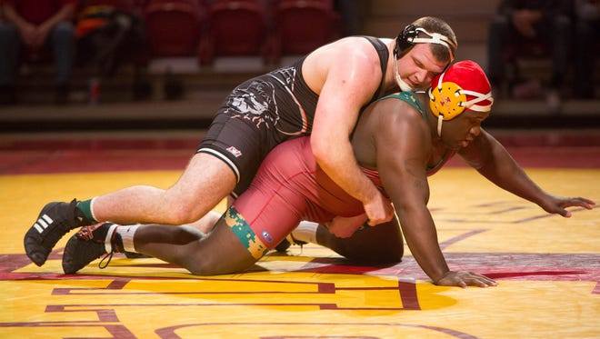Iowa State University's Quean Smith struggles with Oklahoma State's Austin Marsden in the 285-pound match Sunday during their dual meet at Hilton Coliseum in Ames. Marsden held of Smith and secured the win for Oklahoma State.