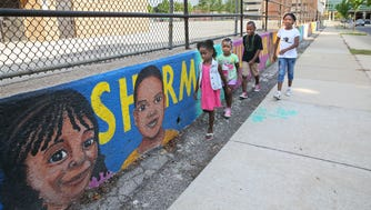 A sidewalk mural depicts the students of Sherman Elementary School.