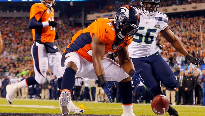 In this Feb. 2, 2014, file photo, Denver Broncos' Knowshon Moreno reaches for a loose ball after the snap passed teammate Peyton Manning, left, during the first half of the NFL Super Bowl XLVIII football game, in East Rutherford, N.J. Seattle Seahawks' Cliff Avril approaches at right. Moreno dove on it for a safety. Seattle defeated Denver 43-8.