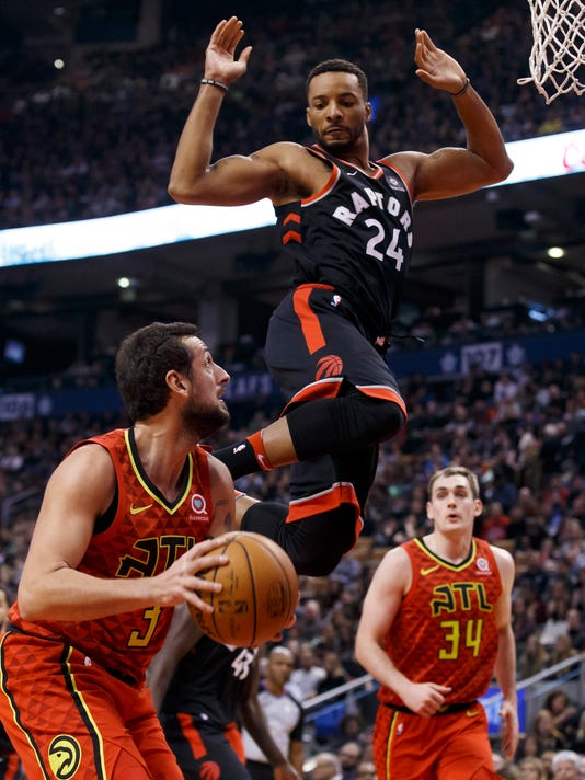 Toronto Raptors forward Norman Powell (24) jumps while defending Atlanta Hawks guard Marco Belinelli (3) during the first half of an NBA basketball game Friday, Dec. 29, 2017, in Toronto. (Cole Burston/The Canadian Press via AP)