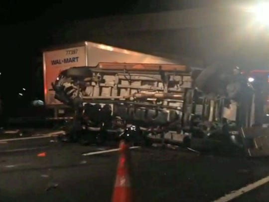 This image from video shows the limousine bus that carried Tracy Morgan and six other people on its side on the New Jersey Turnpike after an accident involving a Walmart tractor-trailer (in background).