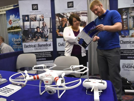 Shanelle Sloan Davis, left, and Terence Henriod work the UNR engineering booth at a day devoted to drones during the Manufacturing in Nevada conference at the John Ascuaga's Nugget on  Thursday.