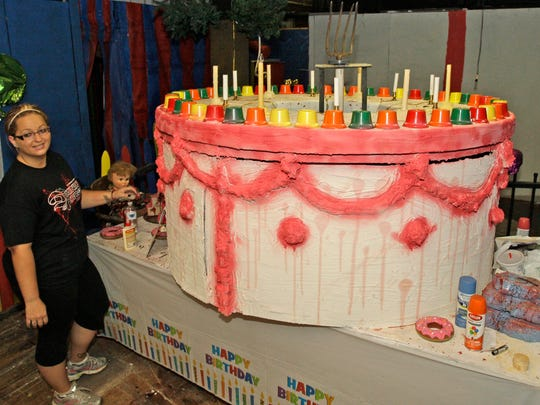 Dominion of Terror co-chairman Jenna Van Der Sande stands by an outsized birthday cake to celebrate the haunted house's 40th birthday.