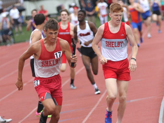 Shelby's Caleb Brown hands off the baton to Blake Lucius in the 3200 meter relay during the Division II semi finals on Friday at Jesse Owens Memorial Stadium in Columbus.