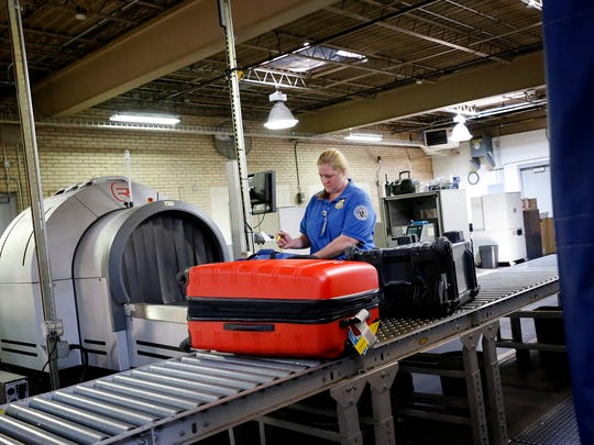 An Elmira Corning Regional Airport employee scans and checks luggage Wednesday afternoon. With a $58 million renovation project in the future, parts of the airport will be remodeled and updated, including the baggage-sorting area.