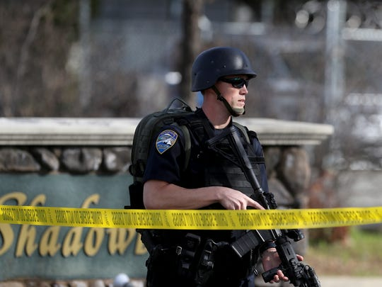 A Redding police officer arrives at the scene as a