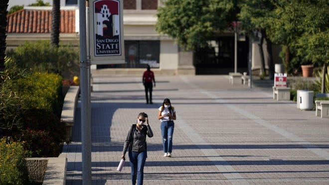 In this Sept. 2, 2020 file photo, people walk on campus at San Diego State University in San Diego. Officials in college towns all over the U.S. are fretting that off-campus students are being counted in places other than the communities where their schools are located.
