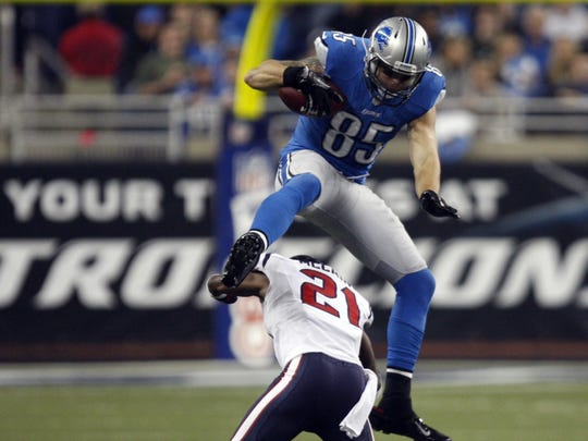 Detroit Lions' Tony Scheffler hurdles the Houston Texans' Quintin Demps during overtime action Thursday, Nov. 22, 2012 at Ford Field.