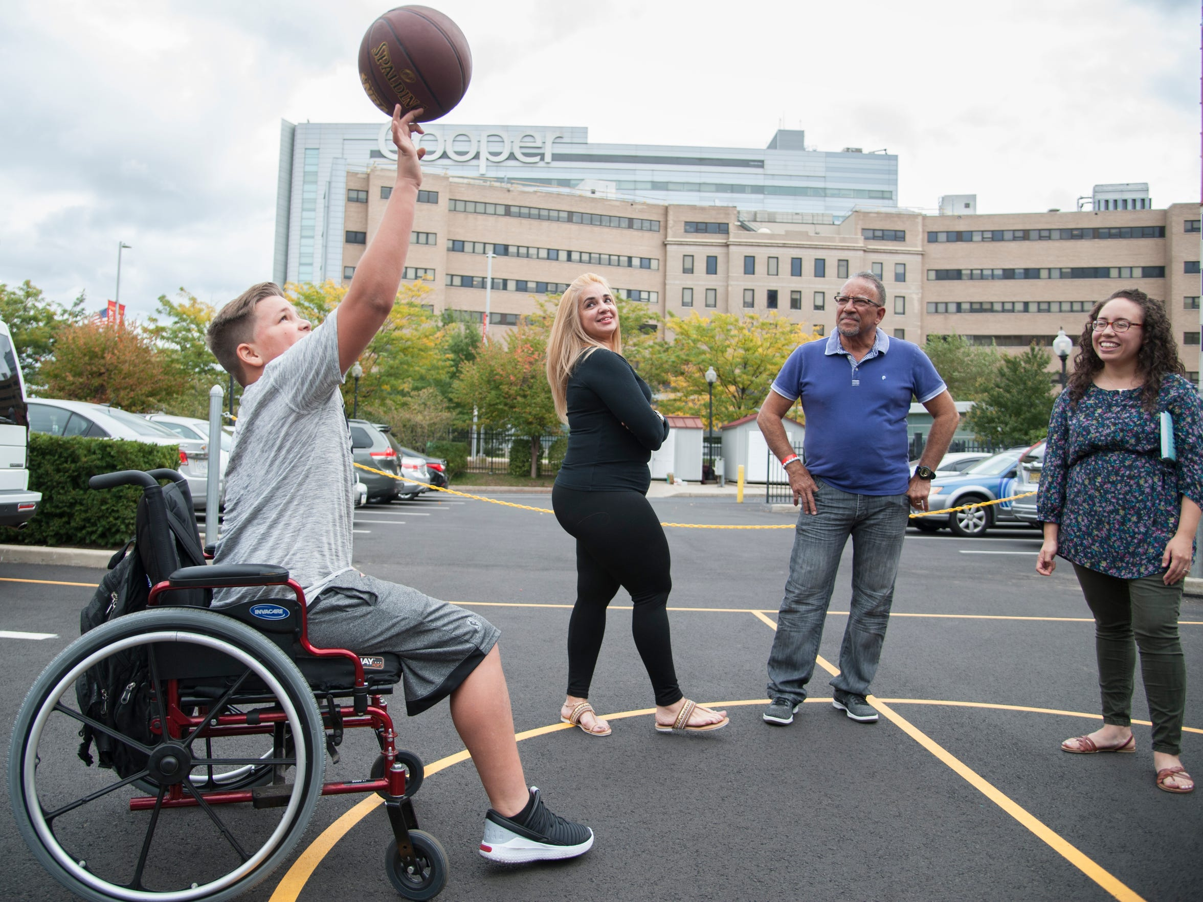 Luis Chiclana, 12 of Puerto Rico, spins a basketball on his finger outside of the Ronald McDonald House in Camden, as (backgound l-r) his mother Joana, father Angel, and translator Sonia Mixter-Guzman watch.  .   Luis was born without a tiba and fibia and is staying at the Ronald McDonald House in Camden with his parents while undergoing treatment, and will soon receive a prosthetic leg.  Luis and parents will be going back to Puerto Rico later this month.  Luis dreams of challenging his idol Michael Jordan to a game.