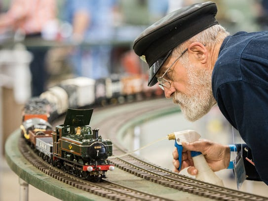 A model train enthusiast cares for a train on the track