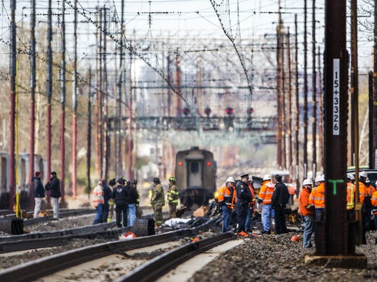 Amtrak and local officials work at the scene of an Amtrak train derailment at the Booth Street railway overpass near Sixth Street after an Amtrak train struck a piece of construction equipment on the tracks in Chester, Pa., on Sunday, April 3, 2016.