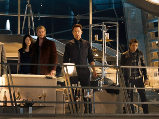 "Cobie Smulders, seated, Chris Evans, Don Cheadle, Claudia Kim, Chris Hemsworth, Robert Downey Jr., Jeremy Renner, Mark Ruffalo and Scarlett Johansson in the film, ""Avengers: Age Of Ultron."""