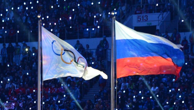 An Olympic Games flag and a Russian flag waving during the closing ceremony of the Sochi Olympics.