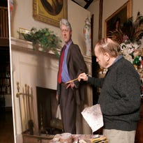 With a replica of the fireplace in the Oval Office set up in his studio, artist Nelson Shanks works on a portrait of former president Bill Clinton. There is a blue dress set up in the studio casting a shadow on the set. Shanks recently told reporters that the shadow represents Monica Lewinsky.