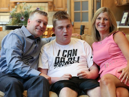 Brian Long, left, and Kim Long, right, pose with their son Brennan Long, 17, who was injured while being restrained at JCPS. June 16, 2016