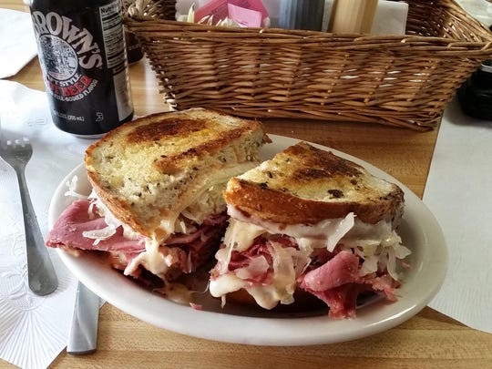 Rita's Ruben Ritual, a corned beef sandwich on rye bread with sauerkraut, Swiss cheese and Russian dressing, sits on a table at Larry's Lunch Box waiting to be eaten.