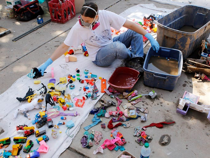 Lisa Dunlap cleans mud off toys on Sept. 19 in Longmont, Colo.