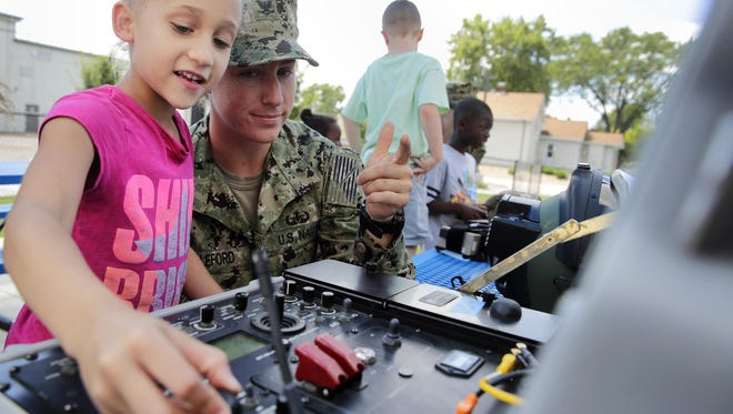 Carolyn Willeford, an explosive ordinance disposal technician with the U.S. Navy, works with Sophia Kelly, 6, as she controls a TALON robot on July 24 at the Menasha Boys and Girls Club. The event was part of Green Bay-Fox Cities Navy Week.