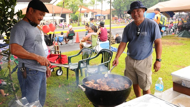 Peter Crisostomo, left, and Joe Certeza keep an on eye on chicken on the grill during the 2014 Liberation Day Parade on July 21 in Hagatna. PDN file photo