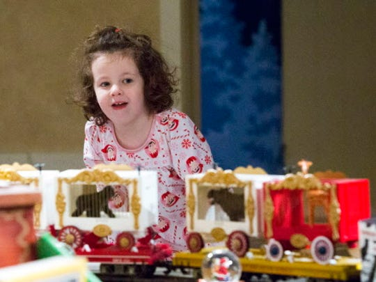 McKenna Spaulding, 3, watches trains in the Christmas Village at Country Springs Hotel.