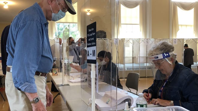 Gordon Miller, left, checks in with ballot clerk Rebecca Beers upon arriving at the Kennebunk Town Hall to vote during the state primary on Tuesday, July 14, 2020.
