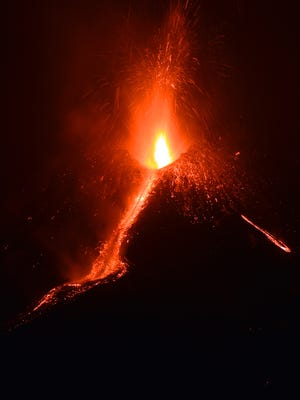 """Lava flows from the Mount Etna volcano on the southern Italian island of Sicily, near Catania, on December 6, 2015 at night. The volcano on the Mediterranean island threw up an ash column some seven kilometres (4.3 miles) high with lava flowing from the Voragine crater for the first time in two years, the National Institute of Geophysics and Vulcanology (INGV) said. The eruption, which began on December 3, 2015, is among the most """"energetic of the past 20 years,"""" added the INGV.  AFP PHOTO / GIOVANNI ISOLINO / AFP / GIOVANNI ISOLINO        (Photo credit should read GIOVANNI ISOLINO/AFP/Getty Images)"""