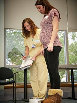During a CenteringPregnancy session, medical assistant Ashley Sullivan records vitals for mother-to-be Kristen Koene.