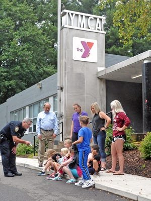Community relations officer Matt Cruise of the Wooster Police Department presented a check on behalf of the Wooster Citizens Police Academy Alumni Association to kids at the YMCA to match the money they made at a recent car wash.