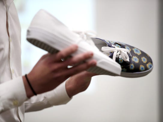 Evan Arnold, a senior at Neenah High School, holds a prototype of what a shoe created through their business Palette could look like during a pitch event for their INCubator course Wednesday at Neenah High School