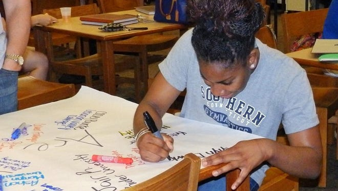 Kylyn Dawkins, a senior at Cumberland Regional High School, adds her name and the name of the college she plans to attend, Southern Connecticut State University, to a banner displayed during a breakfast reception to celebrate college-bound seniors at the school.