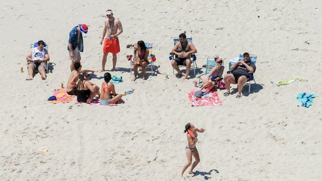 In this Sunday, July 2, 2017, photo, New Jersey Gov. Chris Christie, right, uses the beach with his family and friends at the governor's summer house at Island Beach State Park in New Jersey.
