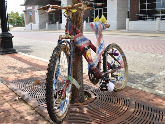 A decorated bike chained to a tree in front of The Town Talk.