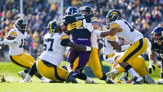 Northwestern running back Justin Jackson (21) is tackled by Iowa defenders during the Hawkeyes' 40-10 win Saturday.