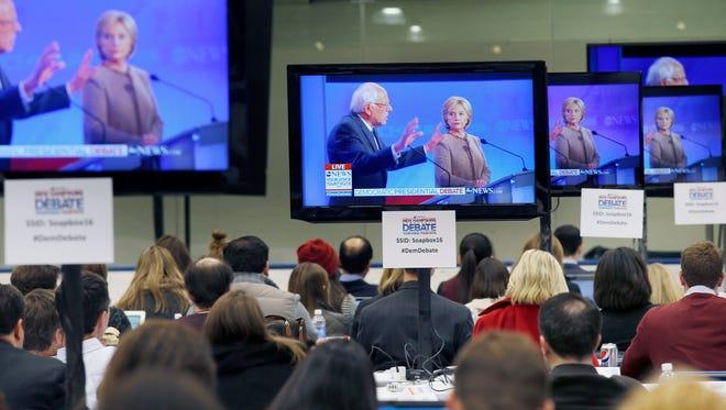 Bernie Sanders, left, speaks as Hillary Clinton listens during a Democratic debate shown on TV screens in the media filing room on Dec. 19, 2015, in Manchester, N.H.