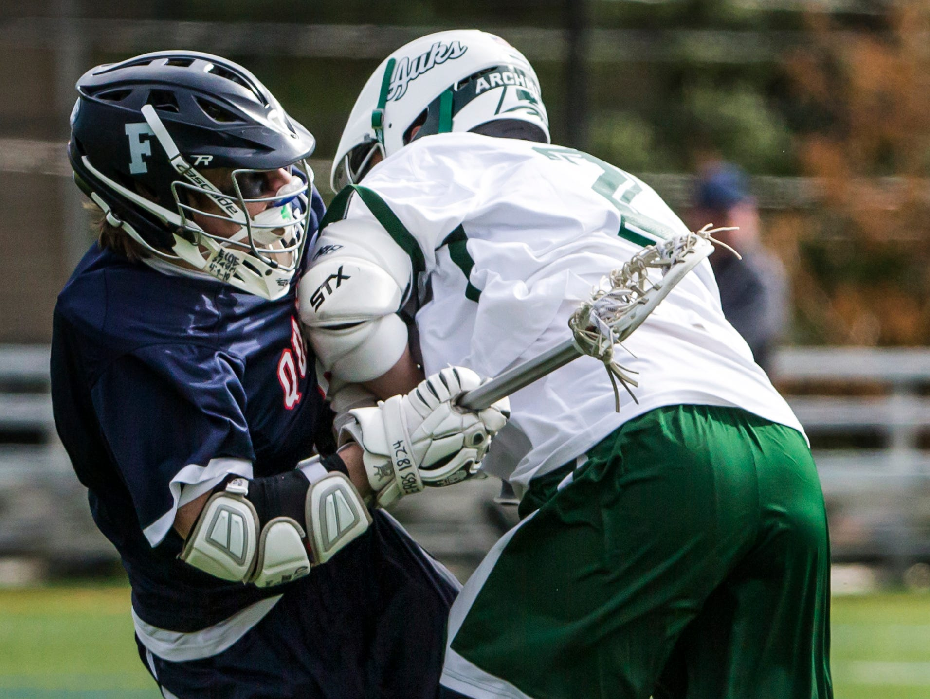 Wilmington Friends' River Harper takes a hit after a shot on goal from Archmere's Connor Dennewitz in Archmere Academy's 13-8 win over Wilmington Friends School at Archmere on Thursday afternoon. Harper scored on the play.