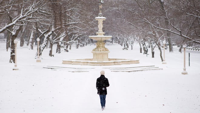 Cody Ritchie walks toward the Josephine Fountain as snow falls in Brandywine Park in Wilmington on Jan. 6, 2015.