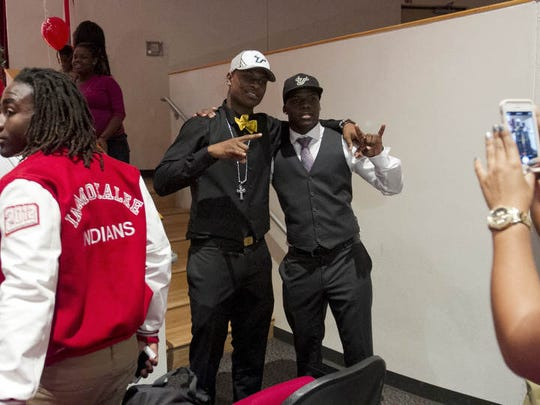 Jimmy Bayes and D'Ernest Johnson are photographed together after signing to play football for the University of South Florida on Wednesday at Immokalee High School.