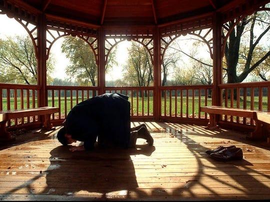 Ali prays in a gazebo on his 88-acre estate in Michigan in 1997.