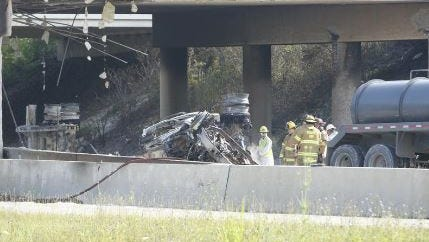 Fire officials stand by an overturned tanker truck that caught fire early Wednesday, July 1, 2015, on Interstate 270 on the West Side where it passes underneath Interstate 70 in Columbus. (Dispatch photo by Kyle Robertson)