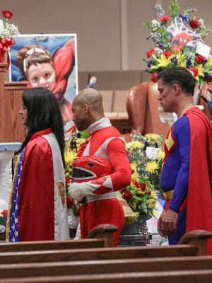 Katie Olvera, left, dressed as Wonder Woman, Aaron Sloan, middle, of Seneca, dressed as a Power Ranger, and John Suber, right, of Greenville, dressed as Superman, pay their respects during a wake service for Jacob Hall, at Oakdale Baptist Church, Tuesday, Oct. 4, 2016 in Townville, S.C. Townspeople and classmates filled a church Tuesday evening to say goodbye to Jacob Hall, a 6-year-old boy who died in a school shooting, filing past a casket adorned with large photos, balloons and a life-size figure of one of his favorite superheroes, Batman.