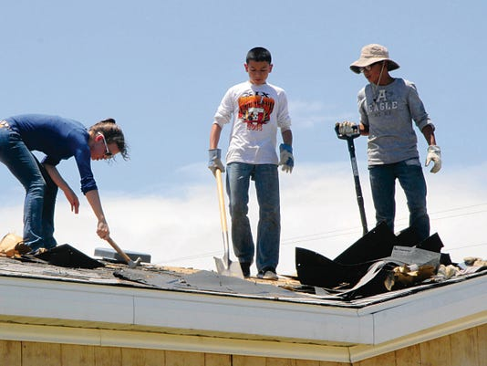 Rachel Twaddle, 15, left, Jarek Najar, 14, center, and Nate Najar, 14, right, work to remove remnants of a roof of a Carlsbad home. The teens were giving time to the project, which was one of 20 projects being worked on as part of the annual Mission Carlsbad.