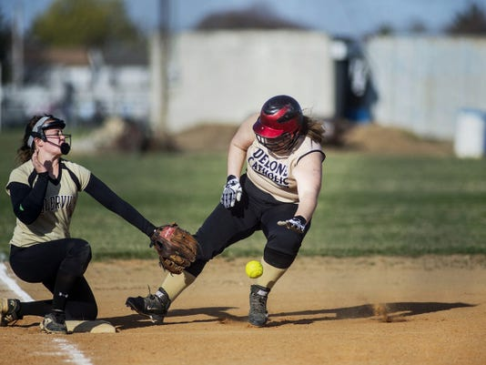 Delone Catholic's Lori Sheaffer, right, arrives safely at third base as Biglerville's Courtney Taylor waits for the ball during Monday's game. The Squirettes won, 12-3.
