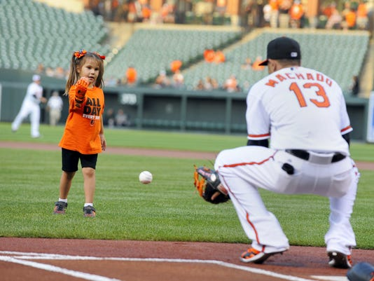 """Hailey Dawson, a 5-year-old from Las Vegas, throws the ceremonial first pitch before a game between the Baltimore Orioles and Oakland Athletics on Monday at Camden Yards in Baltimore. Hailey was born with Poland Syndrome. Engineering students at the University of Nevada, Las Vegas, created the """"Flexy Hand 2"""" that she wore to throw the ball."""