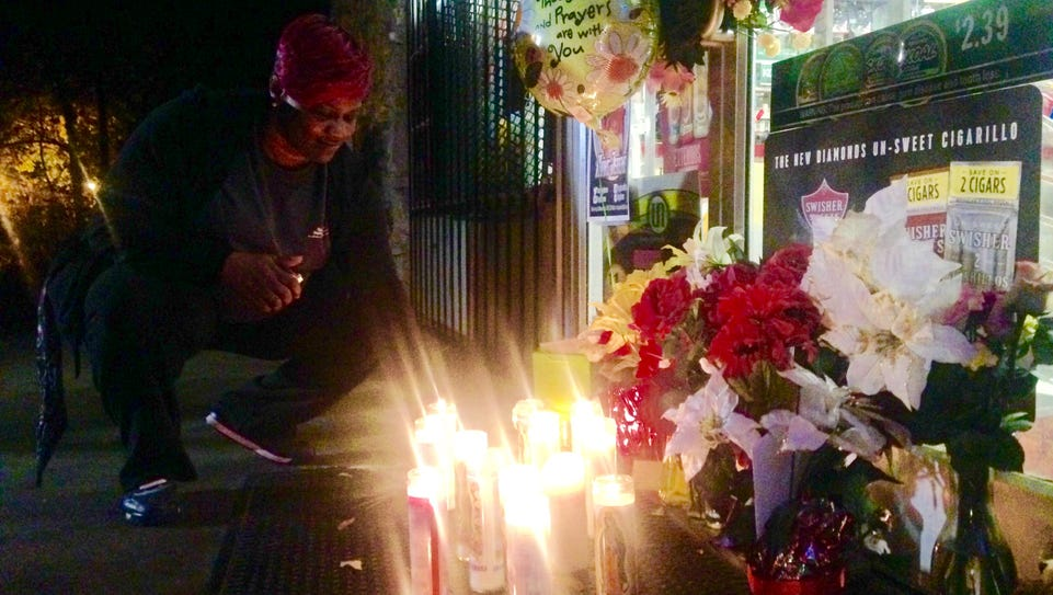 Wilma Jones lights a candle at a memorial site outside