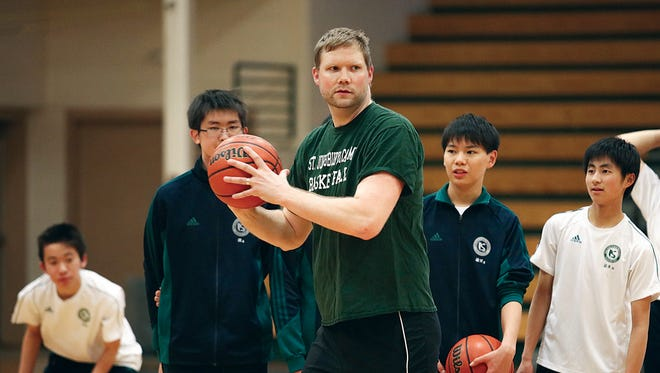 Former UVM and St. Johnsbury basketball star Taylor Coppenrath instructs some Kaijo school students at St. Johnsbury Academy earlier this year. Coppenrath is the new head coach of the Missisquoi girls basketball team.